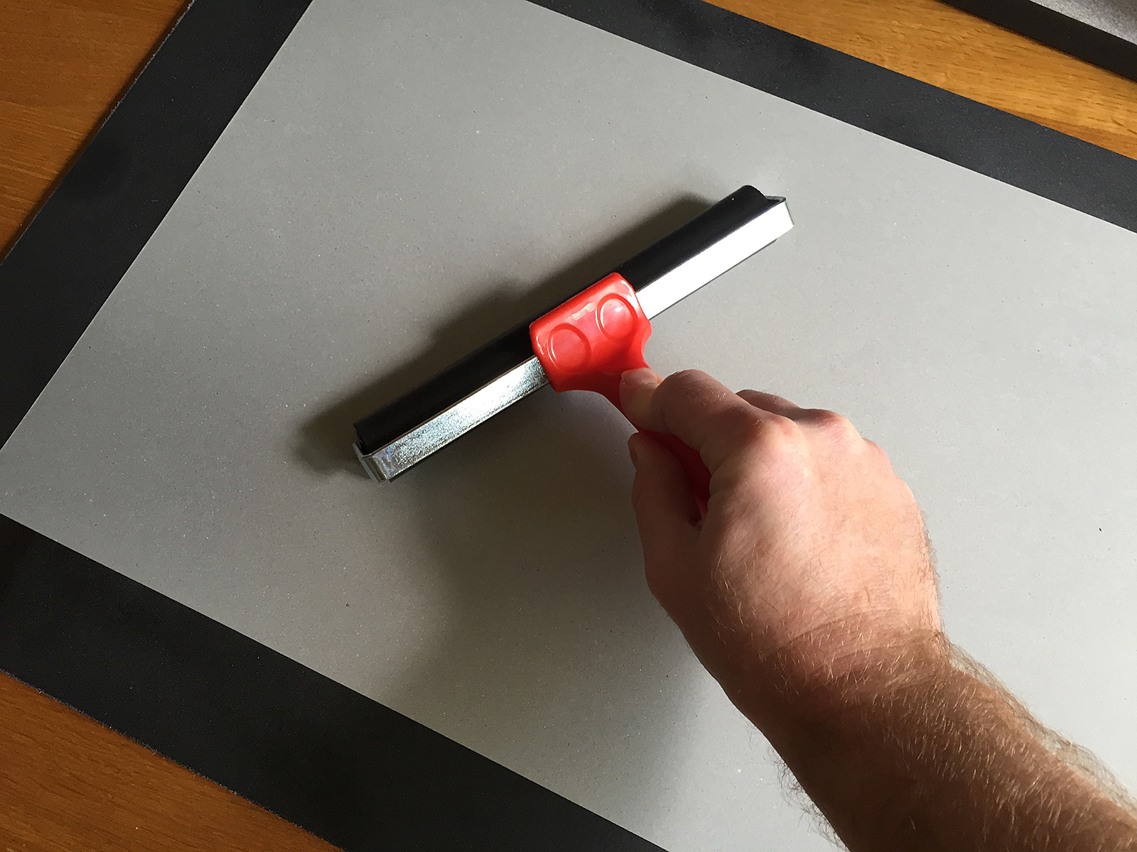 Cover the image with a protective sheet and the use a roller to press the image to the glued surface.